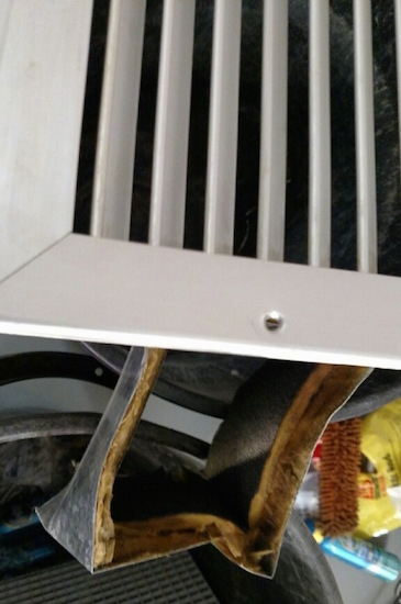 A white vent and a section of a fiberglass liner that was lining the vent