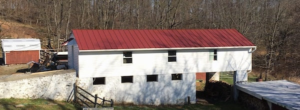A white barn with a red tin roof.