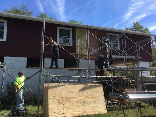 Scaffolding set up in front of the red barn with men taking the fiberglass batts out of the walls. The lower part of the barn is a white stone wall.