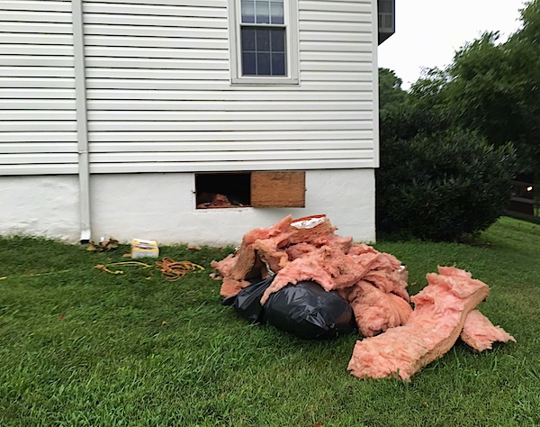 A big pile of pink fiberglass laying in a grassy yard next to an open white farm house crawl space door.