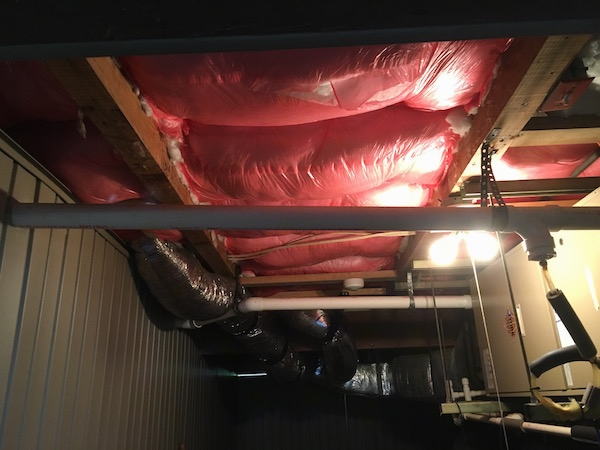 fiberglass insulation tacked to the ceiling on the lower level of a beach house with flex ducts and electric panels and pipes near it