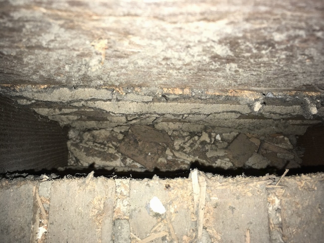 Looking into the cavity of an attic floor that was under a  HVAC system. The area is tan and dirty.