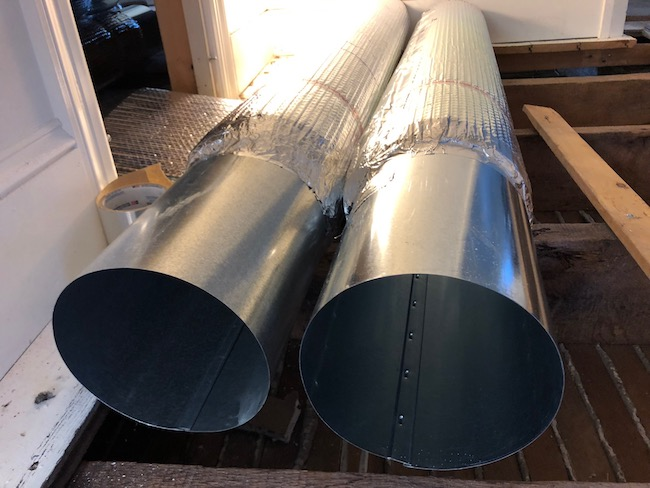 Two metal ducts with shiny bubble wrap around it laying across wooden floor joists