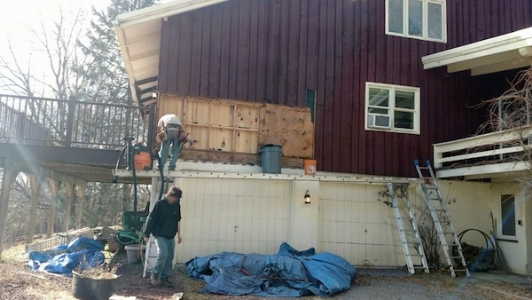 Two men working on a house with the T1-ll removed showing behind the walls where the blown in fiberglass was removed.