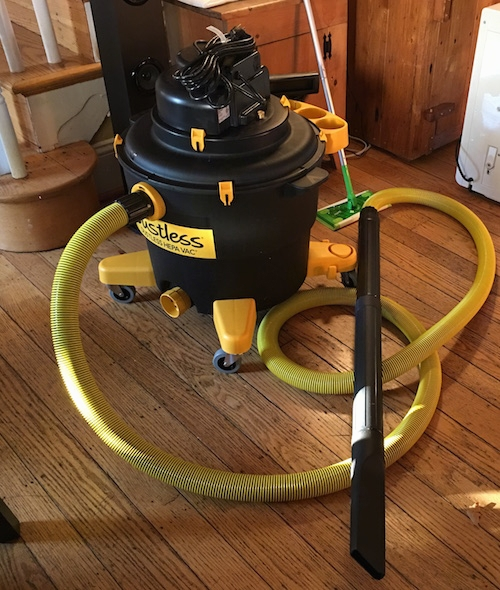 A black and yellow shop vac sitting on a hardwood floor in front of a set of stairs. There are two wooden cabents and a swiffer mop behind it.