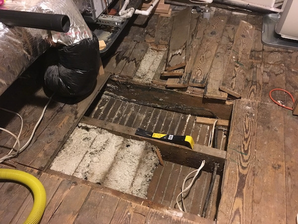 A view looking down at a wooden floor with floor boards removed showing thick white blown in fiberglass in the floor cavity. There is a cental air unit to the left