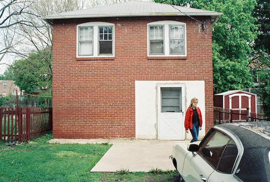A square brick building with a white door and upstairs windows with a cement slab in the front on the ground. There is a girl with blond hair and a red jacket and blue jeans walking towards a white car.