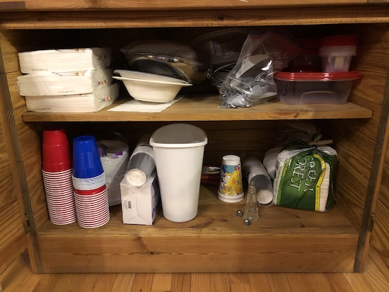 A wooden cabinet full of throw away plastic cups, plastic utensils, paper plates, napkins and other party supplies