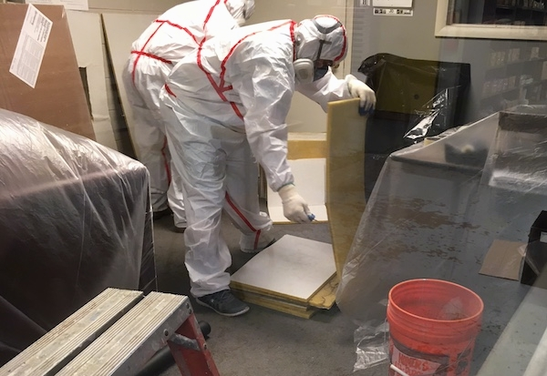 Two men wearing hazmat suits, respirators and gloves inside of an offfice that has plastic covering up all of the office furniture. The first man is picking up one of the many fiberglass ceiling panels.