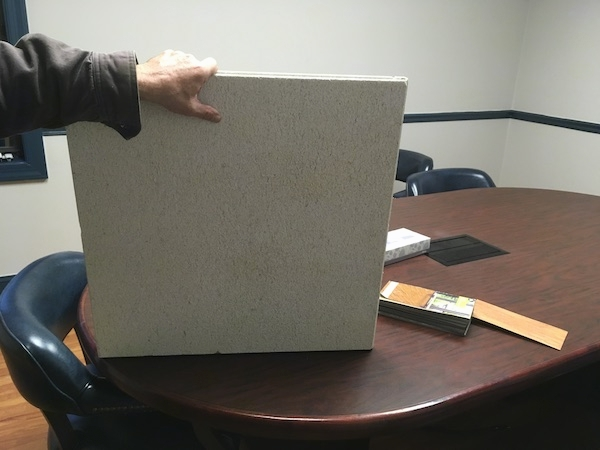 A man's hand holding a square white ceiling tile up on a brown desk inside of an office.