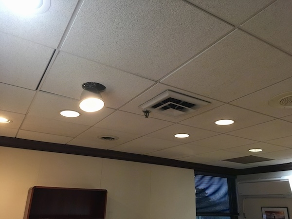 The ceiling of an office with square white tiles with lighting and duct work vents in it.