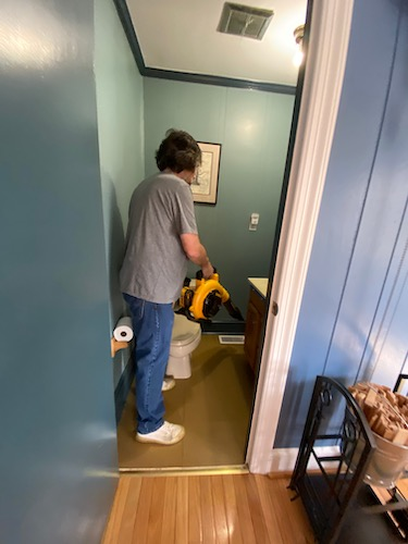 A man in a blue shirt holding a yellow and black Dewalt battery powered leaf blower in a blue half bath off of a kitchen