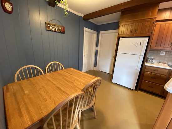 Two closed white doors in a kitchen with a wooden table and a sign on the wall that says Cowgirls Rule