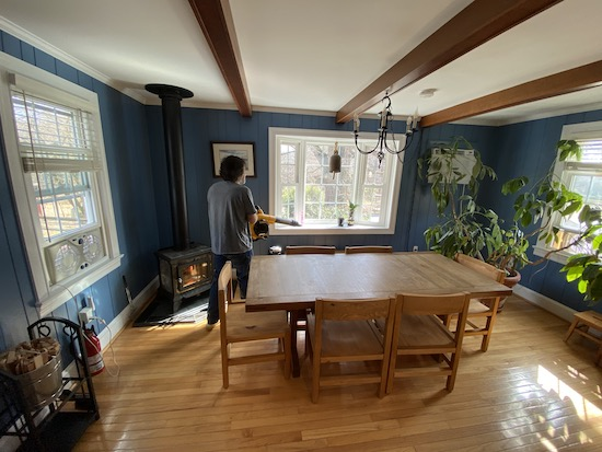 A man in a blue shirt holding a yellow and black Dewalt battery powered leaf blower blowing air to the corner of a dining room.