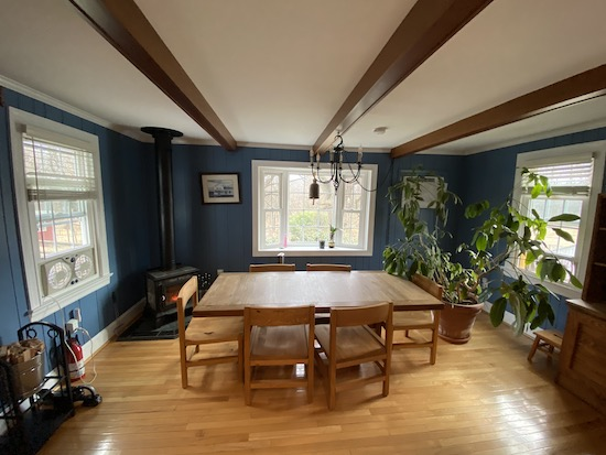 A blue dining room with a This End Up wooden table and chairs in the middle with a wood burning stove and two fans on each end blowing air outside