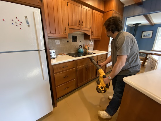 A man in a blue shirt holding a yellow and black Dewalt battery powered leaf blower blowing air in the cracks between a stovetop and the cherry counters below