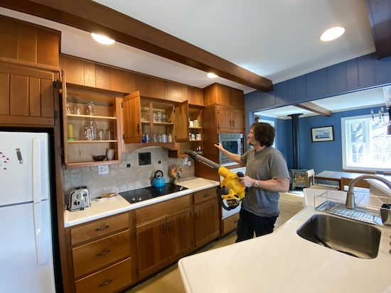 A man holding a yellow and black Dewalt battery powered leaf blower up to a kitchen cabinet full of glasses and dishes