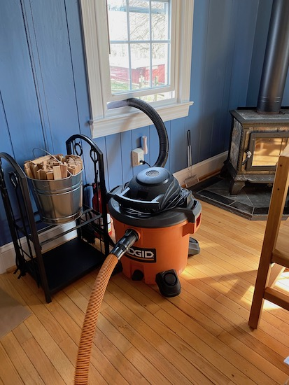 An orange and black shop vac with the exhaust tube out the window next to a wood burning stove