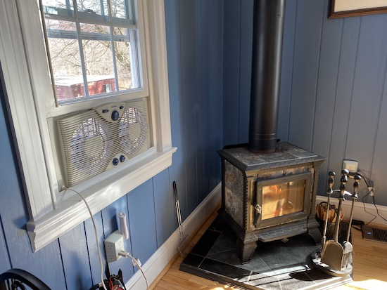 A white exhaust fan blowing air out a window next to a lit wood burning stove