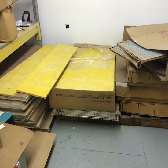 Piles of yellow fiberglass commercial ceiling panels in brown cardboard boxes sitting on top of a gray floor behind a white wall that has a hole in the drywall.