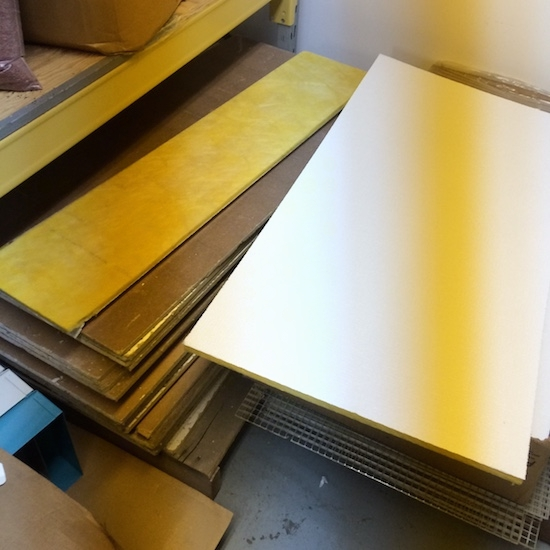 Stacks of yellow fiberglass commercial ceiling panels in brown cardboard boxes sitting on top of a gray floor in front of a white wall.