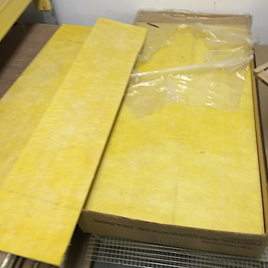 Two piles of yellow fiberglass commercial ceiling panels in brown cardboard boxes sitting on top of a gray floor in front of a white wall.