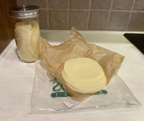 A package of sliced provolone cheese sitting on top of brown wax paper with a blass mason jar full of cheese behind it on a white countertop