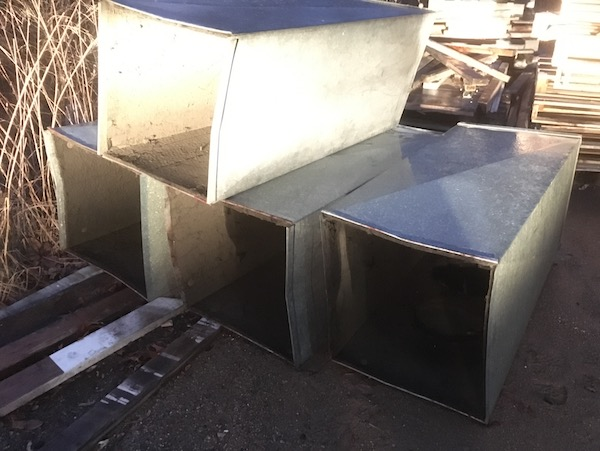 A stack of big square silver metal air ducts outside placed next to piles of wooden boards and wooden skids.