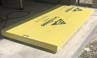 A sheet of yellow drywall laying outside on concrete