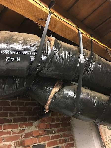 Close up - Two big black round flex ducts running across the length of a feed store. The ducts have exposed fiberglass showing in the seams. There is a brick wall behind them.
