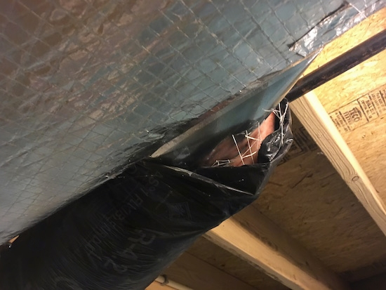 black flex duct work in a basement ceiling with the fiberglass ends exposed to the air next to a larger silver air duct