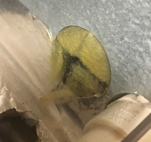 Close up of yellow fiberglass coming out of a round hole that was cut at the bottom of a heater.