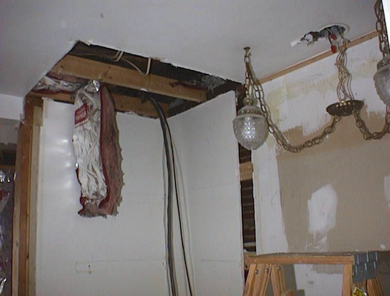 A dining room in a house with a hole cut in the ceiling and a fiberglass bat hanging down from the top. There is also a light fixture and a ladder.
