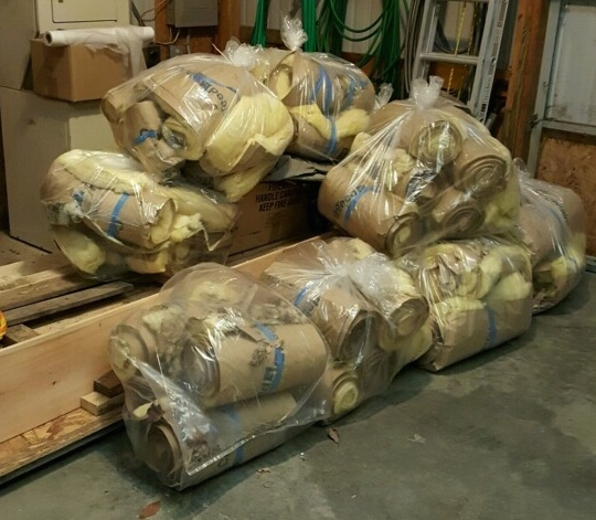 Clear trash bags on a floor full of rolls of yellow fiberglass bats piled up awaiting to be tossed into the dumpster.