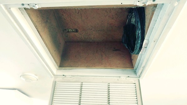 An open vent on a white ceiling with fiberglass walls and a flex duct off to one end.