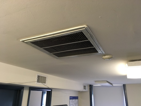A white air vent on a ceiling of an office.