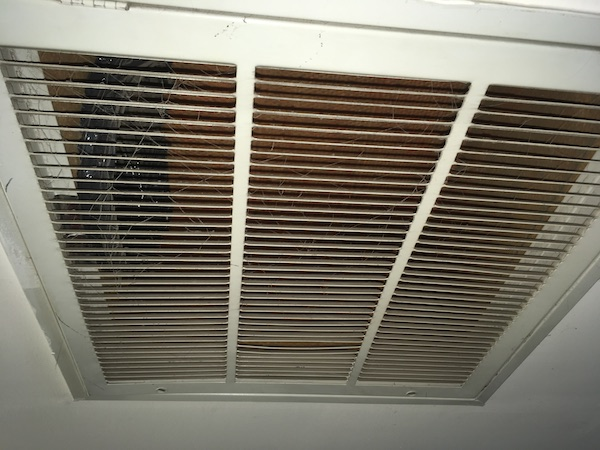 Close up of a white vent on a ceiling inside of an office.