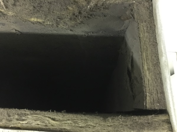 Looking down the inside of a fiberglass lined duct. It has a thick layer of dirt on top of the paper liner. The glass is falling apart and so is the outer paper.