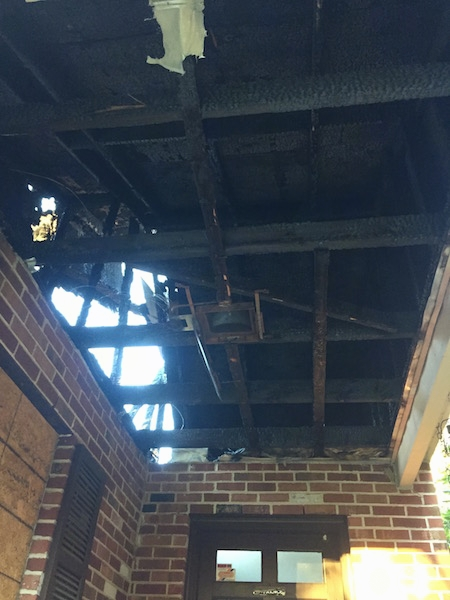 Looking up into the ceiling of a house that burned down. The walls are brick and the beams are chared.