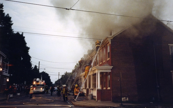 A street in a town of row homes with smoke coming from the end house. There are fire fighters with a ladder against the house.