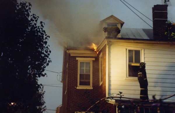 The second floor of a house with flames coming from the roof and a couple of firemen on the roof. There is smoke coming from the house.