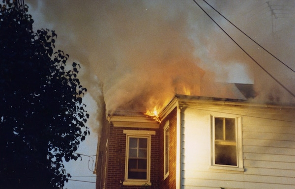 Flames coming out of the roof of a house.