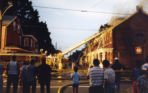 A street in a town of row homes with smoke coming from the end house. There are fire fighters with a ladder against the house spraying water on it and a crowd of people watching from the street.