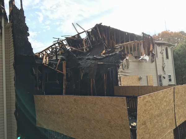 The backside of a tan townhome that burned down in a fire.