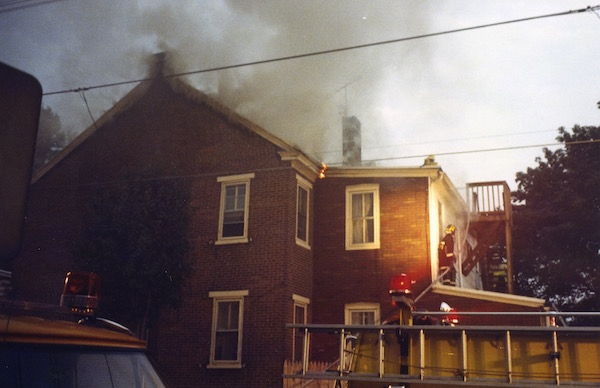 A brick house with smoke coming from it and fire fighters walking on the roof.