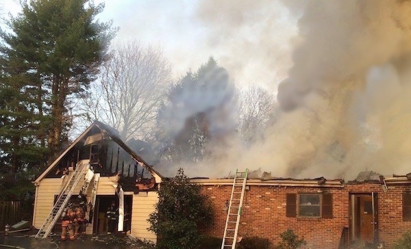 A burning house with a ladder leaning on the side of it, the roof gone and smoke coming from it.