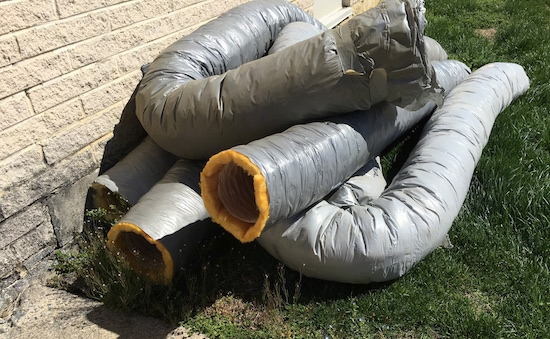 A pile of flex ducts laying outside which were removed from a building