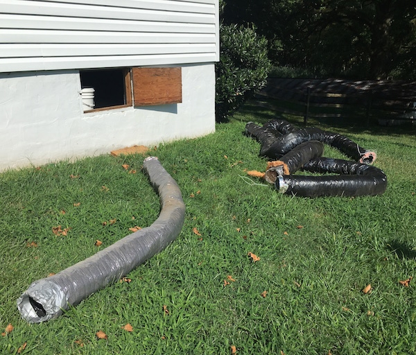 Long tubes of black flex ducts laying out in a grassy yard next to a white house with a crawl space door open to the house.