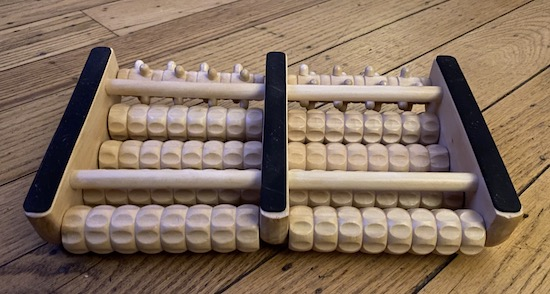 The backside of a wooden foot massager with roll pins