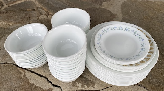 A set of shiny white dishes with some having a blue heart with green leaf, and a brown decorative pattern around the rims